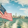 New York and Manhattan skyline from Hudson river with American Flag - Vintage filtered look with tilted horizon — Stock Photo #52782505