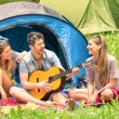 Group of best friends singing and having fun camping together - Concept of carefree youth and freedom outdoors in the nature - Caucasian young people during vacations — Stock Photo #52782543