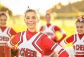Portrait of an happy young cheerleader in action outdoors - Group of girlfriends during cheerleading sport training at high school — Stock Photo
