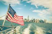 New York and Manhattan skyline from Hudson river with American Flag - Vintage filtered look with tilted horizon — Photo