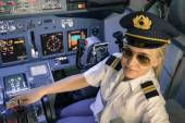 Beautiful blonde woman pilot wearing uniform and hat with golden wings - Modern aircraft cockpit ready for take off - Concept of female emancipation — Stock Photo