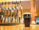 RIMINI, ITALY - OCTOBER 11, 2014: pint of beer served in a pub. Guinness is a world famous Irish dry stout created in the brewery of Arthur Guinness (1725-1803) at St. James's Gate in Dublin. — Foto de Stock