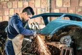 Young man mechanical worker repairing an old vintage car body in messy garage - Safety at work with protection wear — Foto Stock