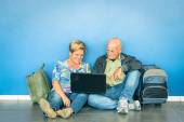 Happy senior couple sitting on the floor with laptop waiting for a flight at the airport - Concept of active elderly and interaction with new technologies - Travel lifestyle without age limitation — Stock Photo
