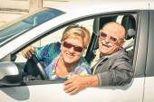 Happy senior couple ready for driving a car on a journey trip - Concept of joyful active elderly lifestyle with man and woman enjoying their best years — Stock Photo