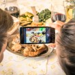 Couple of boyfriend and girlfriend taking a food selfie in dinner restaurant - Moda of catching the instant with modern smartphone at lunch meeting with typical italian food — Stock Photo #55978979
