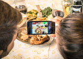 Couple of boyfriend and girlfriend taking a food selfie in dinner restaurant - Moda of catching the instant with modern smartphone at lunch meeting with typical italian food — Stock Photo