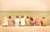 Group of international multiracial friends sitting at the beach talking with each other and contemplating the sea - Concept of multi cultural friendship against racism - Warm vintage filtered look — Photo