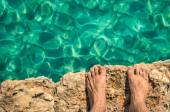 Naked human barefoot on rock cliff ready to jump in the clear blue water - Comino and Gozo blue lagoon in Malta - Freedom and carefree lifestyle during travel and vacation in exclusive destinations — Stock Photo