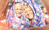 Senior happy couple taking a selfie at the week clothes market traveling around the world - Concept of active elderly and interaction with new technologies and trends — Stock Photo