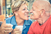 Happy playful senior couple in love tenderly enjoying a cup of coffee - Joyful elderly active lifestyle - Man having fun and smiling with her wife in a bar cafe restaurant during vacation — Foto de Stock