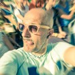 Bald funny man taking a selfie in the crowd with stupid tongue out expression - Travel lifestyle enjoying moment of carefree loneliness - Vintage filtered look — Foto Stock #56172501