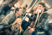 Group of young hipster friends having fun interaction and talking in subway train - Vintage filtered look with radial defocusing - Concept of youth and friendship — Photo