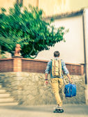 Young hipster man moving forward with his longboard holding his trolley backpack - Modern concept of freedom and alternative lifestyle - Cheap travel backpacking around the world — Stock Photo