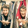 Young hipster brothers at the weekly cloth market - Best friends sharing free time having fun and shopping in the old town in a sunny day - Guys enjoying everyday life moments — Stock Photo #57387691