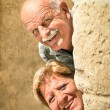 Happy senior couple in love during retirement - Joyful elderly lifestyle with man and woman with funny playful attitude - Visiting the old town during a sightseeing tour — Stock Photo #57387709