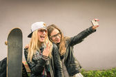 Hipster girlfriends taking a selfie in urban city context - Concept of friendship and fun with new trends and technology - Best friends eternalizing the moment with modern smartphone — Photo