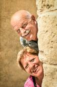 Happy senior couple in love during retirement - Joyful elderly lifestyle with man and woman with funny playful attitude - Visiting the old town during a sightseeing tour — Stock Photo