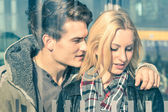 Affectionate couple of lovers behind glass reflections - Young man whispering magic words in the ear of his beautiful girlfriend - Beginning of a love story on a vintage filtered look — Stock Photo
