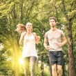 Happy couple jogging in the park - Young man and woman sharing workout and sport activity - Male and female fitness models running together in the nature at sunset — Stok fotoğraf #58094715