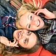 Best friends enjoying time together outdoors with smartphone - Concept of new technology with two girlfriends having fun on a vintage wood bench and red pillows — Stock Photo #59000967