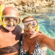 Senior happy couple taking a selfie at Blue Lagoon in Gozo and Comino - Travel to mediterranean island of Malta - Concept of active elderly and fun around the world experimenting new technologies — Stock Photo #59001083