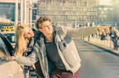 Young couple of lovers dealing with a taxi cab in the city center - Handsome man and beautiful woman explaining street directions to taxicab - Sunny day of a love story on a warm vintage filtered look — Stock Photo