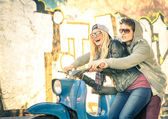Young couple of lovers haviing fun on a vintage scooter moped - Handsome man in playful attitude with his beautiful girlfriend - Beginning of a love story on a warm sunny winter day — Stock Photo