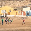 LUDERITZ, NAMIBIA - 24 NOVEMBER 2014: local young people playing football in the playground next to a modern township. For lucky and talented players, soccer is a fast way to escape poverty of slums — Stock Photo #59388747