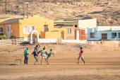 LUDERITZ, NAMIBIA - 24 NOVEMBER 2014: local young people playing football in the playground next to a modern township. For lucky and talented players, soccer is a fast way to escape poverty of slums — Stock Photo