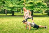 Girlfriend mocking her boyfriend while training in the park - Young man and woman during spring workout and sport activity - Male and female happy couple fitness models exercising after running — Stock Photo