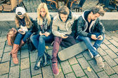 Group of young hipster friends playing with smartphone with mutual disinterest towards each other - Modern situation of technology interaction in alienated lifestyle - Internet wifi connection — Stock Photo