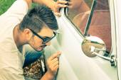 Young handsome man with sunglasses inspecting a vintage car body at second hand trade - Passion and transportation lifestyle of a retro classic vehicles collector — Stock Photo