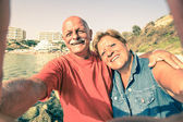 Senior happy couple taking a selfie at Blue Grotto resort in Malta south coast - Adventure travel to mediterranean islands - Concept of active elderly and fun around the world with new technologies — Stock Photo