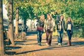 Group of happy best friends with alternative fashion look walking at the park - Hipster tourists having fun outdoors in sunny winter day - University students during a break hanging out together — Stock Photo