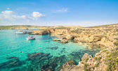 The world famous Blue Lagoon in Comino island - Mediterranean nature wonder in the beautiful Malta - Unrecognizable international tourist people and snorkeling divers - Exclusive travel destinations — Stock Photo