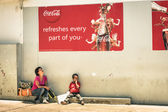 WINDHOEK, NAMIBIA - NOVEMBER 27, 2014: namibian mother and son sitting on floor under a Coca Cola poster. The country has a population of 2.1 million people and a multi-party parliamentary democracy — Zdjęcie stockowe