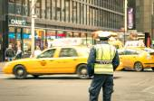 NEW YORK CITY - 22 DECEMBER, 2013: unidentified NYPD officer on the streets of Manhattan with yellow taxi cabs. Established in 1845, NYPD is the largest municipal police force in the United States — Stock Photo