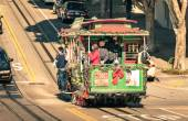 SAN FRANCISCO, UNITED STATES - DECEMBER 15, 2013: people riding a Powell Hyde cable car at Hyde Street. With twenty-three lines, the city cable system is the world's last manually operated service. — Stok fotoğraf