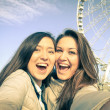 Young women girlfriends taking a selfie at luna park with ferris wheel - Concept of friendship and fun with new trends and technology - Best female friends catching the moment with modern smartphone — Stock Photo #62539271