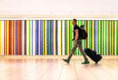 Man walking at international airport with suitcase and backpack - Concept of alternative lifestyle traveling around the world - Young hipster traveler in hurry for airplane boarding after check in — Stock Photo