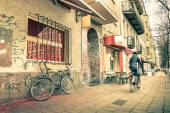 Vintage retro travel postcard of a narrow street in the former east side of Berlin - Mix of past and present in the multicultural capital fo Germany - Everyday life with people and bike on the road — Stock Photo
