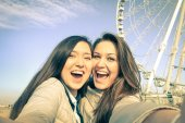Young women girlfriends taking a selfie at luna park with ferris wheel - Concept of friendship and fun with new trends and technology - Best female friends catching the moment with modern smartphone — 图库照片