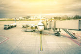 Modern airplane at the terminal gate ready for takeoff - International airport with dramatic sky - Concept of emotional travel around the world on a nostalgic filtered look — Stock Photo