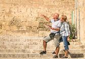Happy senior couple exploring old town of la Valletta with city map - Concept of active elderly and travel lifestyle without age limitation - Trip to european mediterranean wonders — Stock Photo
