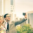 Modern couple taking a selfie at business center outdoors - Concept of love and interaction with new technologies and trends - Everyday life and positive feelings in urban financial district — Stock Photo #62860887