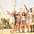 Group of multiracial happy friends cheering at ferris wheel - International concept of happiness and multi ethnic friendship all together against racism for peace and fun - Warm nostalgic filter — Fotografia Stock  #62947405