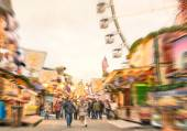 Crowd of people walking at luna park on a radial zoom defocusing - Multicolored fun stands at german Christmas market - Ferris wheel and colorful wooden houses at Berlin amusement area in winter time — Stock Photo