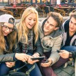 Group of young hipster friends having fun together with smartphone - Modern situation of technology interaction in everyday lifestyle - Internet wifi connection spots outdoors — Stock Photo #63737189