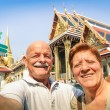Senior happy couple taking a selfie at Grand Palace temples in Bangkok - Thailand adventure travel to asian destinations - Concept of active elderly and fun around the world with new technologies — Stock Photo #64303243